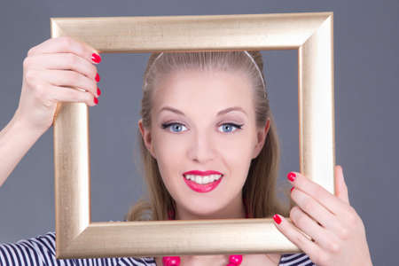 narcissism: attractive blondie pinup girl in striped dress with photo frame over grey Stock Photo