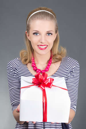 pinup woman in striped dress giving a present photo
