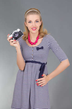 woman in retro clothes with photo camera over grey photo