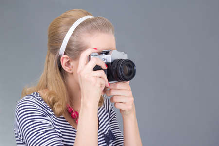 young woman in retro clothes posing with photo camera over grey photo