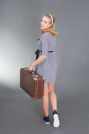 pinup girl with retro suitcase over grey photo