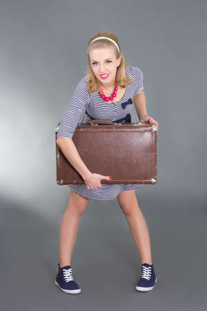 pinup girl posing with brown retro suitcase over grey photo