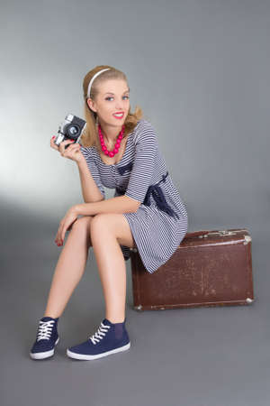 beautiful pinup woman with photo camera sitting on brown retro suitcase photo