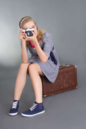 pinup woman with photo camera sitting on brown retro suitcase photo
