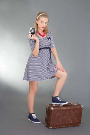 pinup woman posing with camera and brown retro suitcase over grey photo