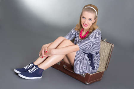 pinup woman sitting in big brown retro suitcase over grey photo