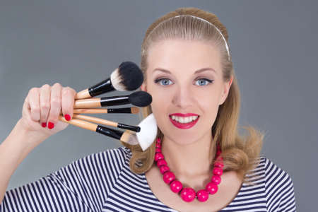 pinup woman with make up brushes over grey Stock Photo - 18959704
