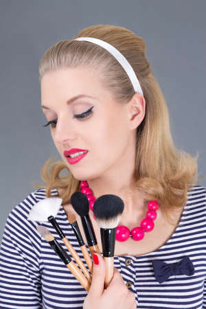 dreaming pinup woman with make up brushes over grey Stock Photo - 18961405