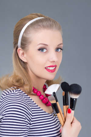 young pinup woman with make up brushes over grey Stock Photo - 18959793