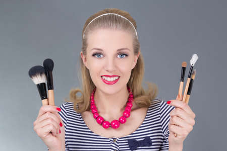 portrait of young pinup woman with make up brushes over grey Stock Photo - 18959692