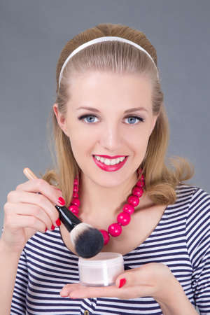portrait of young pinup woman with make up brush and powder over grey Stock Photo - 18960996