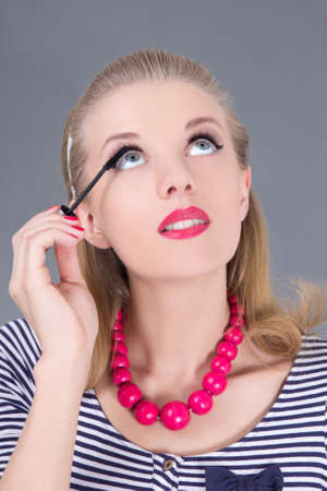 beautiful woman applying mascara make up on eyes by brush Stock Photo - 18958784