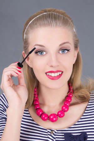 young beautiful woman applying mascara make up on eyes by brush photo