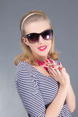 portrait of young attractive pinup girl in sunglasses over grey Stock Photo - 18961396