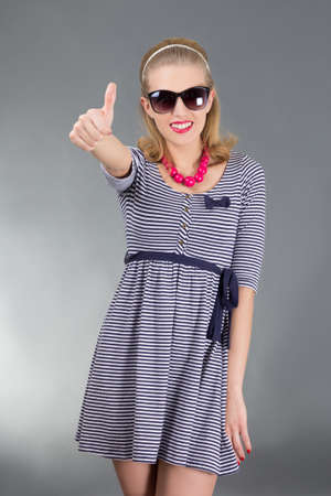 portrait of young attractive pinup girl in sunglasses thumbs up photo