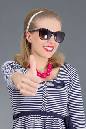 portrait of beautiful pinup girl in sunglasses thumbs up photo