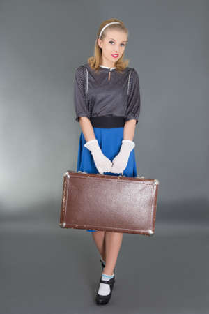 young beautiful pinup girl with retro suitcase over grey background photo