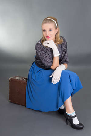 young beautiful pinup girl sitting on retro suitcase over grey background photo