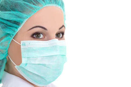 surgical cap: female doctor in mask over white background - close up portrait