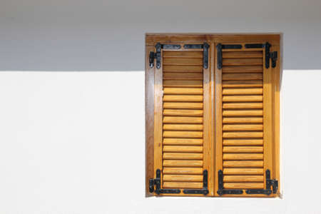 orange vintage window with shutters over white wall photo