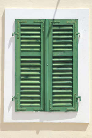 green vintage window with shutters over white wall photo