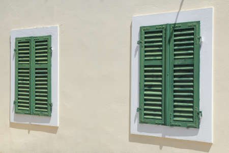 green vintage windows with shutters over white wall photo