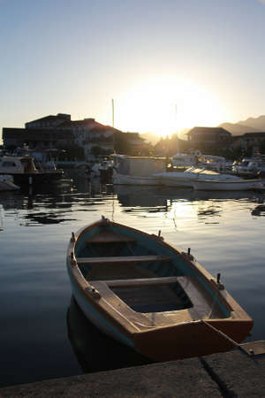 small boat at dramatic sunset in Tivat, Montenegro photo