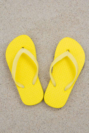yellow flip flops on the white sands of a tropical beach photo
