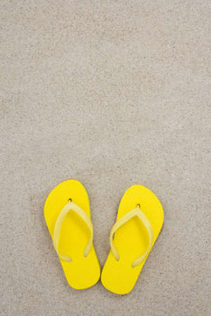 yellow flip flops on the white beach sand with copyspace photo