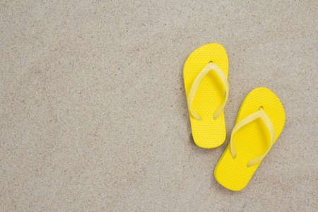 yellow flip flops laying on the sandy beach photo