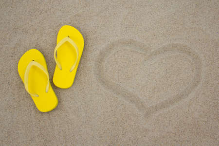 yellow flip flops and heart on white beach sand photo