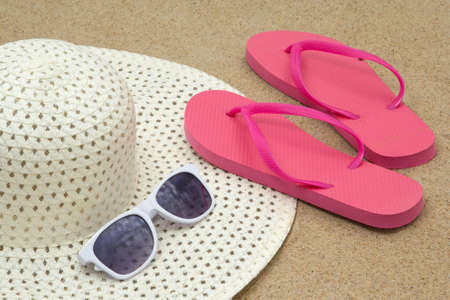 picture of pink flip flops, sunglasses and hat on white beach sand photo