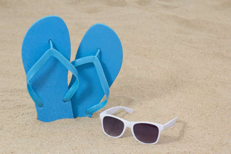 bright blue rubber flip flops and sunglasses on white sand photo