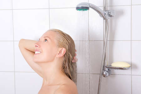 young blondie woman washing hair in shower photo