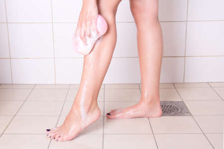 woman washing her legs with sponge in shower photo
