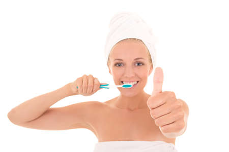 attractive woman with toothbrush and towel thumbs up over white background. hand in focus photo