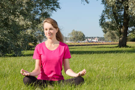 Beautiful happy young woman sitting in park photo