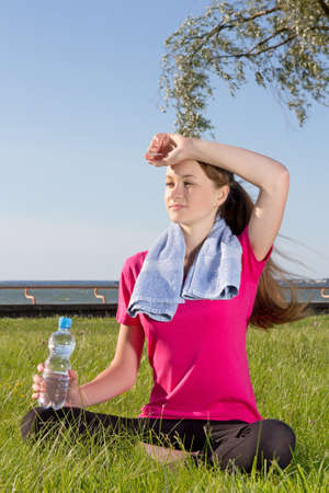 Woman sitting in park with towel and bottle after training photo