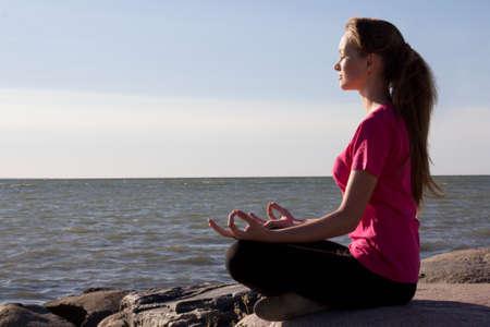 attractive girl in lotus pose sitting near sea photo