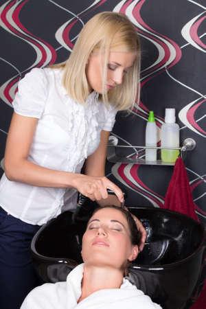 beautiful woman washing hair in salon sink photo