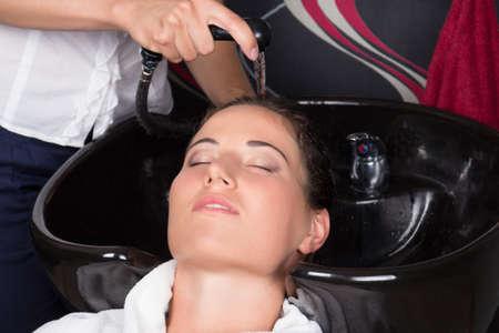 hairdresser washing hair of customer in beauty salon photo