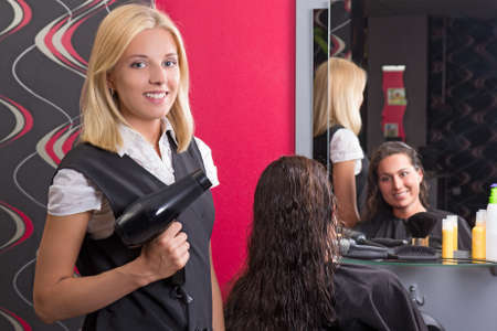young beautiful hairdresser with hairdryer and smiling customer in beauty salon photo