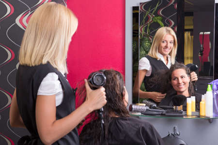 beautiful hairdresser with hairdryer and smiling customer in beauty salon photo