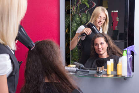 young hairstylist drying womans hair in beauty salon photo