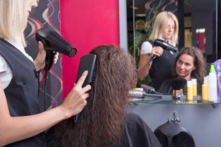 professional hairdresser with hairdryer and hairbrush drying female hair in beauty salon photo