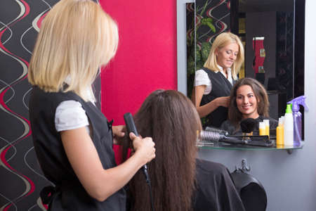 Female hairdresser straightening womans hair with iron in beauty salon photo