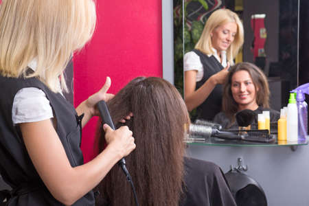 hairdresser straightening womans hair with iron in beauty salon photo