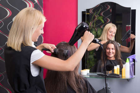 young hairdresser with hairdryer and hairbrush drying female hair in salon photo