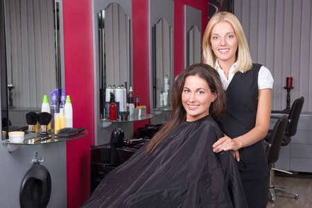 young happy woman in beauty salon getting a hair cut photo
