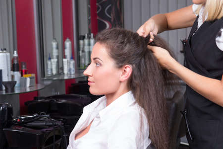young attractive brunette woman in hairdressing salon photo
